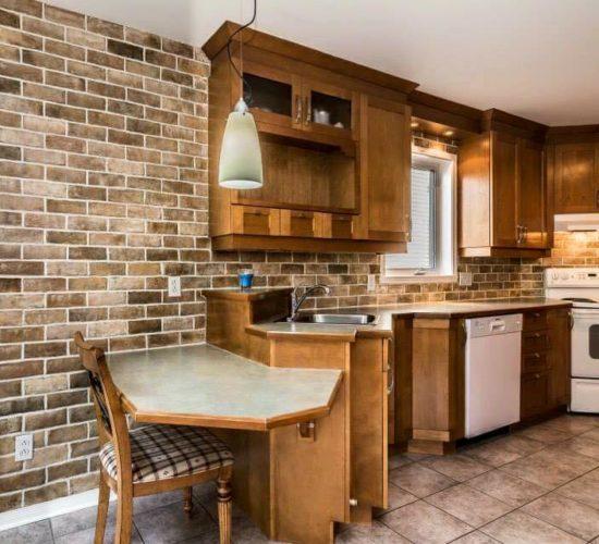 Faux fini de brique avec relief et textures en plâtre, sur mur d'une cuisine